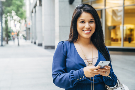 Close up of Hispanic woman texting on cell phone in city Banco de Imagens - 102038154