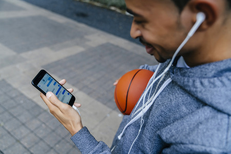 Black man holding basketball listening to cell phone with earbuds