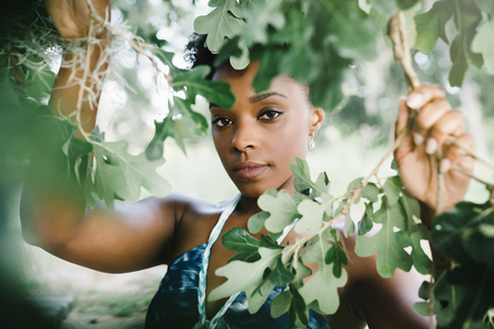 Portrait of serious mixed race woman holding tree branches