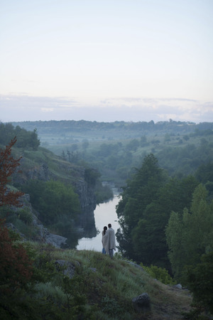 Caucasian couple standing on hill admiring river