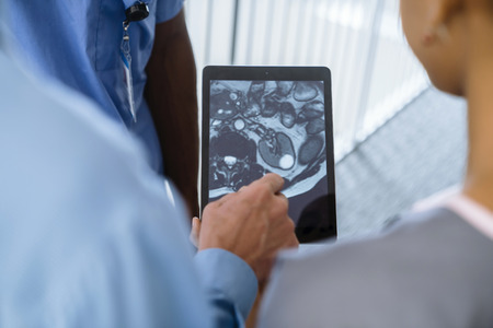Close up of doctor and nurses viewing image on digital tablet