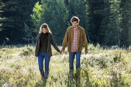 Caucasian couple walking in field holding hands Banco de Imagens - 102038162