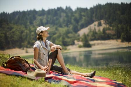 Hispanic woman sitting on picnic blanket near lake Banco de Imagens - 102038164