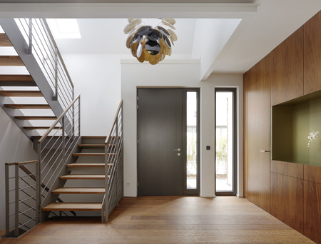 Plank floor and walnut wall covering in home near staircase Banco de Imagens - 102038165