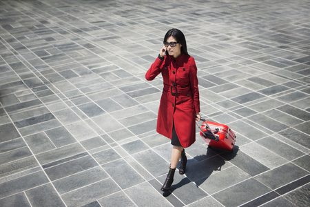 Asian woman pulling rolling suitcase and talking on cell phone
