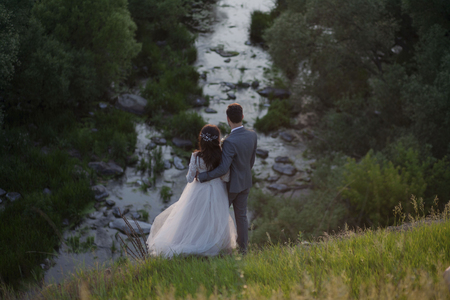 Caucasian bride and groom standing on hill admiring river Banco de Imagens - 102038168