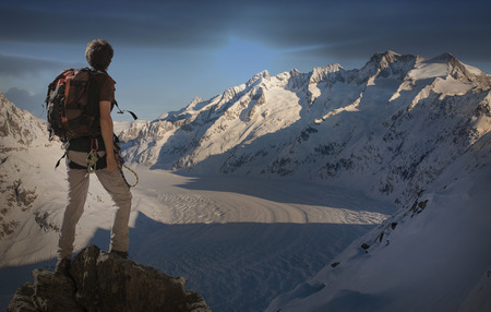 Caucasian man hiking on snowy mountain LANG_EVOIMAGES