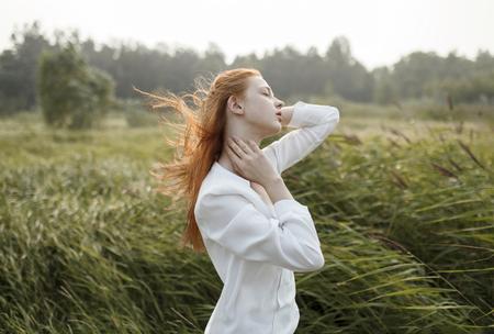 Wind blowing hair of Caucasian woman in field Banco de Imagens - 102038171