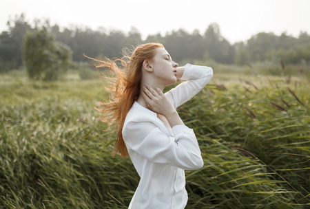 Wind blowing hair of Caucasian woman in field LANG_EVOIMAGES