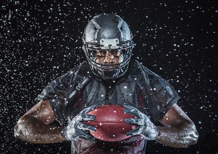 Water splashing on Black football player holding football Banco de Imagens - 102038173