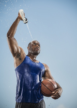 Black man holding basketball cooling off with water bottle