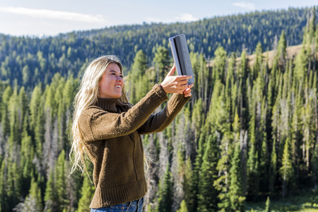 Caucasian girl photographing landscape with digital tablet LANG_EVOIMAGES