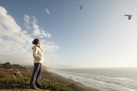 Mixed Race woman standing on beach watching gliders Banco de Imagens - 102038178