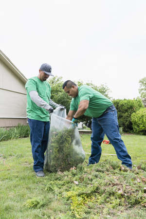 Volunteering men bagging yard debris LANG_EVOIMAGES