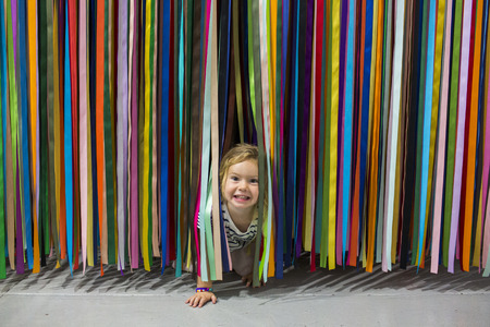 Caucasian girl crawling under colorful hanging streamers LANG_EVOIMAGES