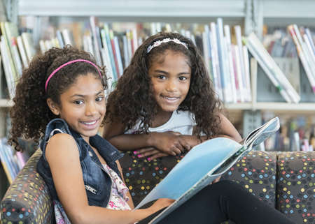 Portrait of smiling mixed race girls on sofa with book in library LANG_EVOIMAGES