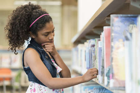 Pensive mixed race girl selecting book at library