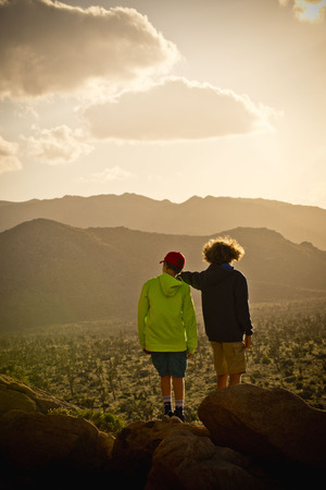 Boys standing on rock admiring desert landscape
