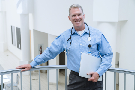Portrait of smiling Caucasian doctor leaning on railing holding laptop