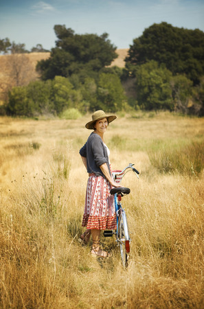 Portrait of smiling Caucasian woman standing in field with bicycle LANG_EVOIMAGES