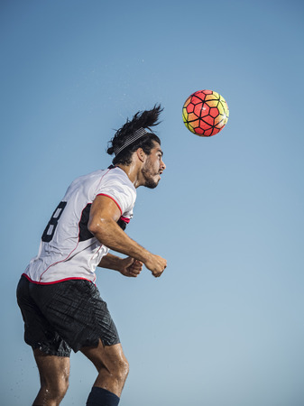 Hispanic man heading soccer ball