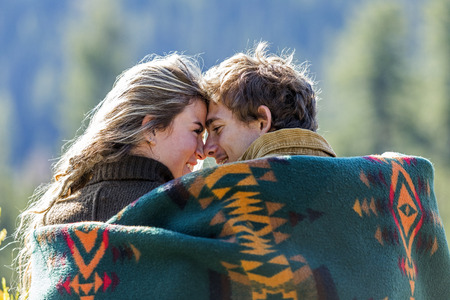 Caucasian couple wrapped in blanket rubbing noses