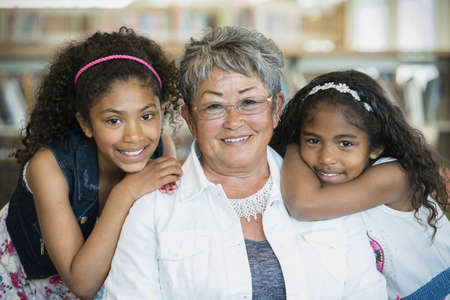 Portrait of smiling teacher and students in library LANG_EVOIMAGES