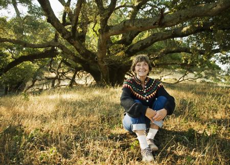 Smiling Caucasian woman sitting near tree Banco de Imagens - 102038197