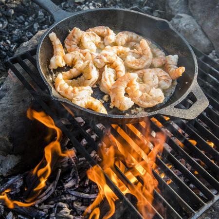 Shrimp frying in skillet over campfire Banco de Imagens - 102038020