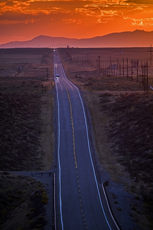 Cars driving on remote road at sunset LANG_EVOIMAGES