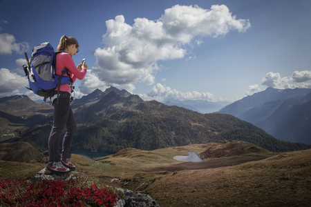 Caucasian woman photographing scenic view of landscape with cell phone Banco de Imagens - 102038198