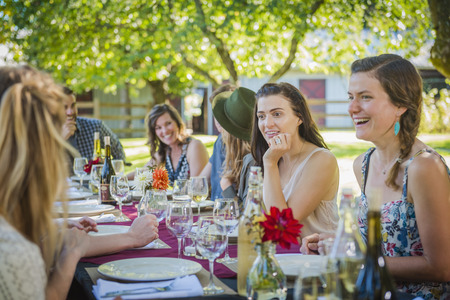 Caucasian women talking at table at party outdoors LANG_EVOIMAGES