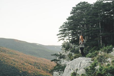 Caucasian woman standing on rock admiring scenic view of landscape LANG_EVOIMAGES