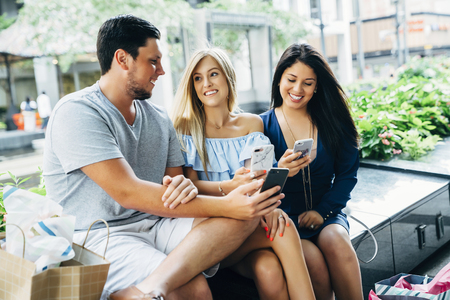Friends sitting on bench texting on cell phones Banco de Imagens - 102038201