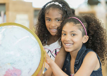 Smiling mixed race girls posing with globe in library