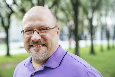 Portrait of smiling Caucasian man in park LANG_EVOIMAGES