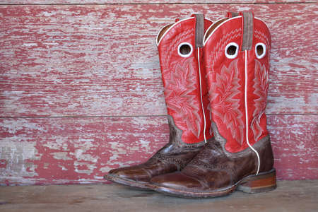 red cowboy boots on red barn board Banque d'images
