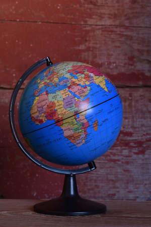 a world globe with a red barn board background Foto de archivo