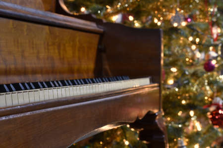 a piano with a Chrismas tree in the background