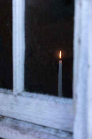 a Candle glowing in a window