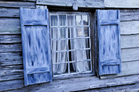 Old blue shutters against blue siding