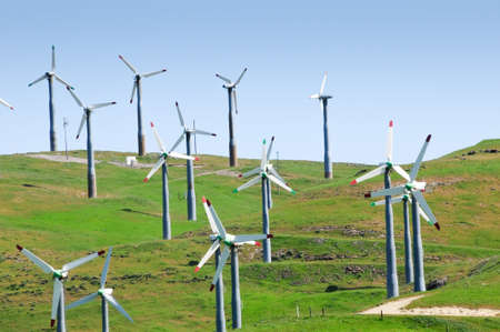 Several wind mills on green rolling hills Stock Photo