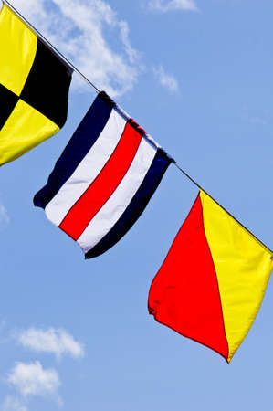 Colorful signal flags flying against blue sky photo