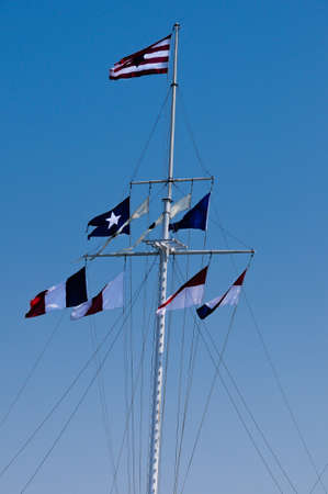 Flags flying on a boat mast with blue sky photo