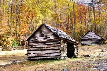 Two historic log cabins in Smoky Mountain National Park with fall colors