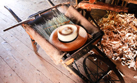 An old wooden wheelbarrow with straw hat and saw Stock Photo