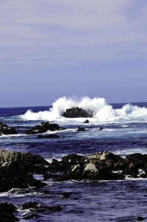 Waves crashing over a rock near Pacific Grove California