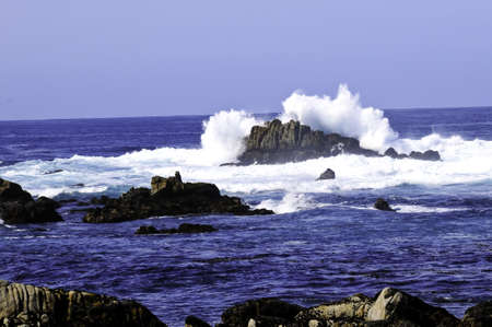 Waves crashing over rocks in the pacific ocean photo
