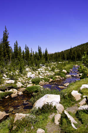 A high sierra stream flowing thru a rocky meadow Stock Photo