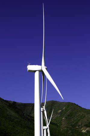 Three wind turbines or windmills against a blue sky Stock Photo